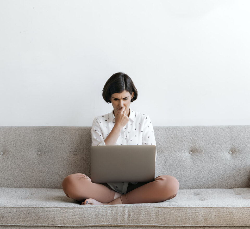 woman behind laptop identifying limiting thoughts