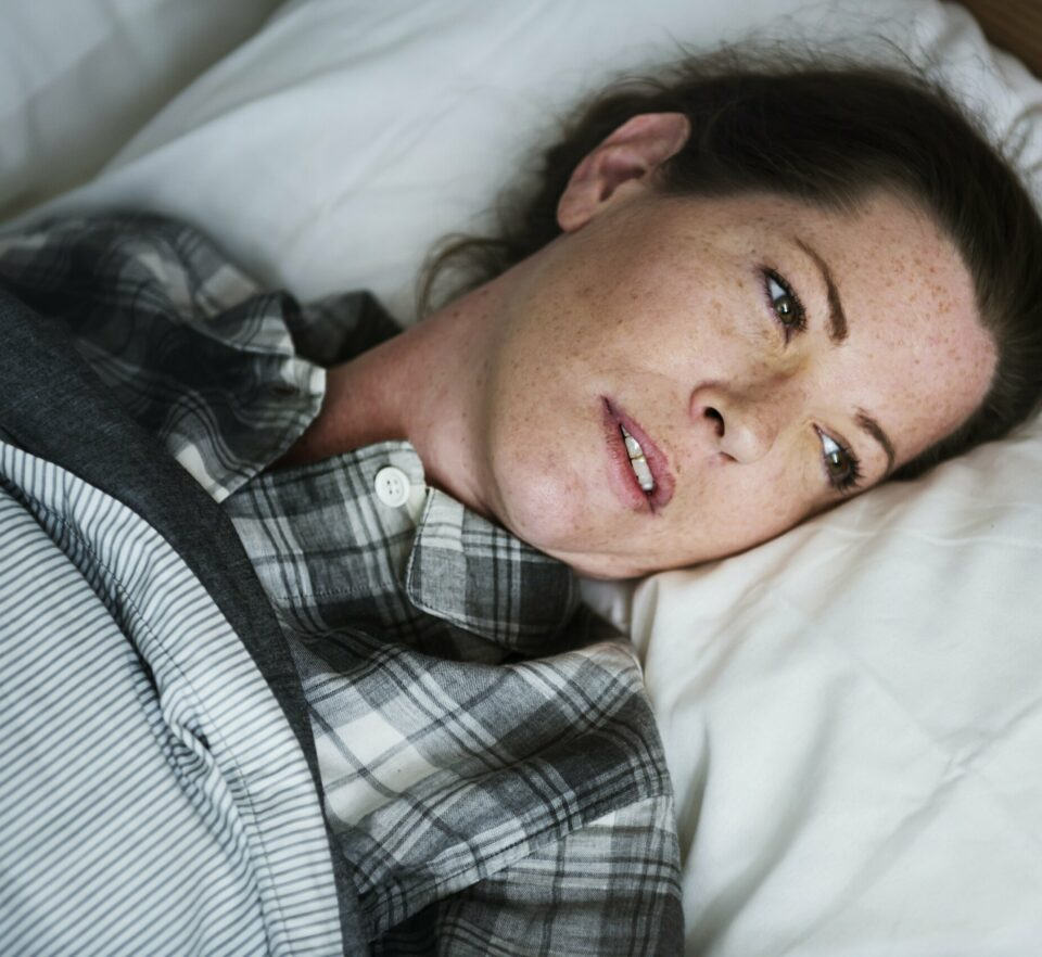 woman in bed suffering from anxiety