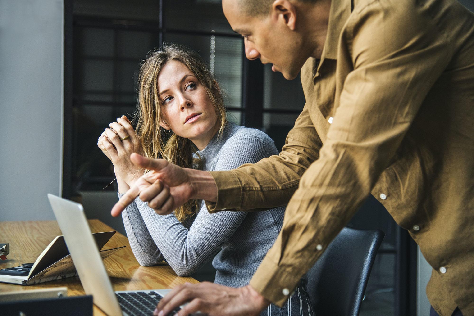 Jeune fille travaillant derrière un ordinateur souffrant de stress au travail