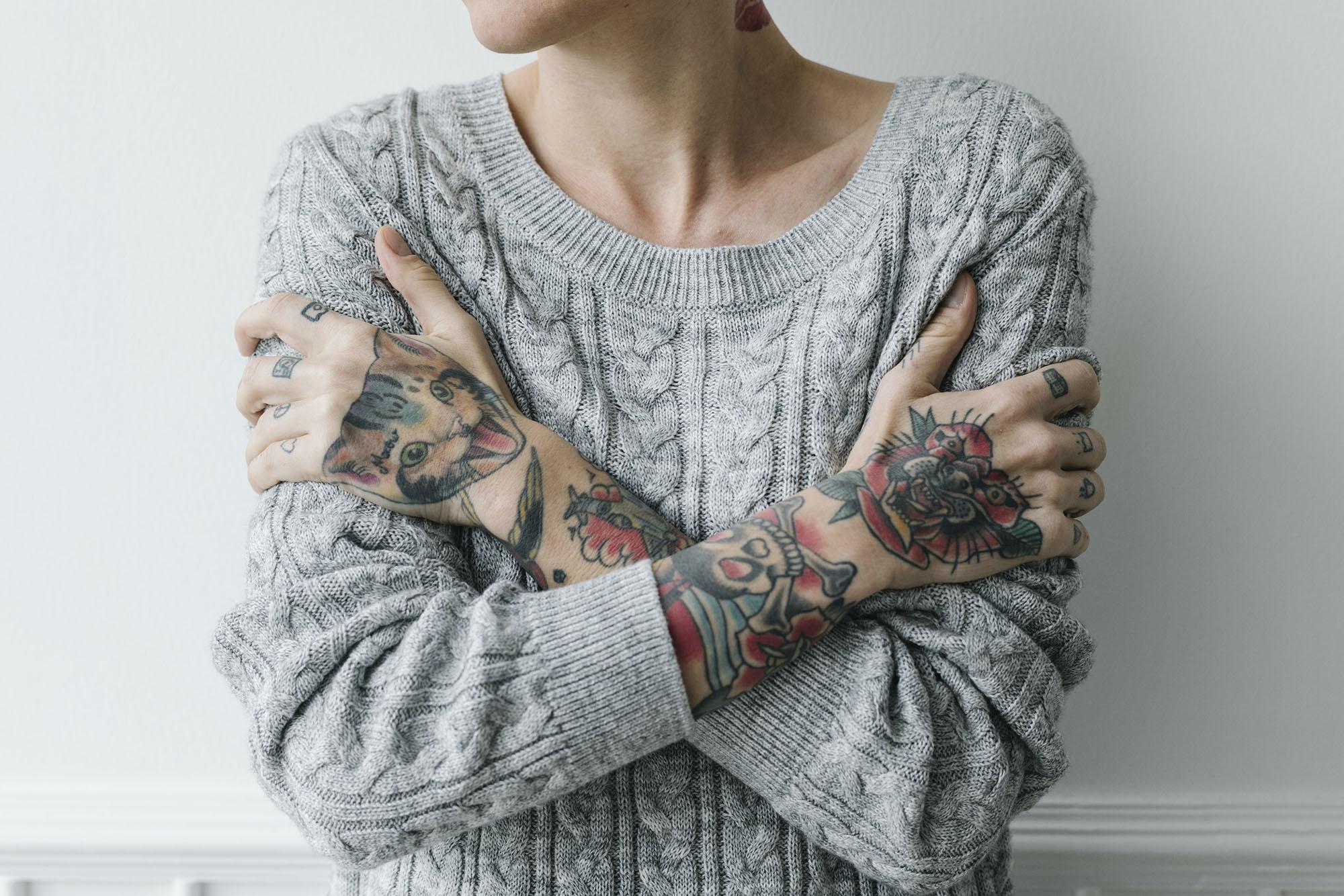 mec avec un tatouage se serrant dans ses bras souffrant d'une faible estime de soi